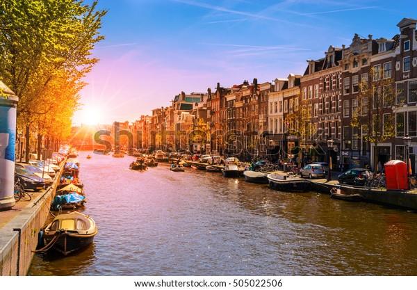 Traditionele oude gebouwen en boten bij zonsondergang in Amsterdam, Nederland
