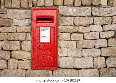 traditional old fashioned English red postbox mounted in a cotswold stone wall