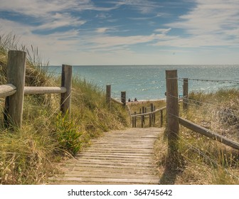 Traditional, old fashioned wooden boardwalk to Littlehampton beach in Sussex.  It is clearly a hot day and the wooden boardwalk curves around to the sea.  The sky is blue with white fluffy clouds.