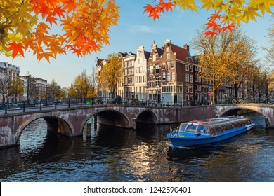 Traditional old houses on canal at fall day in Amsterdam, Netherlands at autumn season.