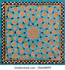 Traditional old Islamic design with flowers and stars made of brown clay and blue tiles in Yazd.