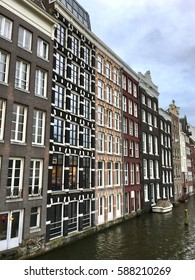 Traditional old living houses with colorful facades stand along canal in central historical part of Amsterdam city