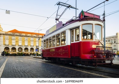 Traditional old red tramcar cable electric trolley stops in Praca do Comercio, main square of the Baixa district of Lisbon, Portugal