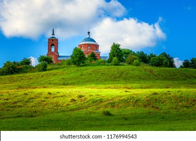 Traditional old Russian Church - summer landscape with blue sky, green hills with grass.