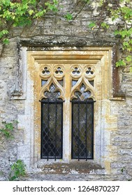 Traditional old rustic double window with glass and gothic surround. With green leaves in front of the brickwork around the window. With space for text.