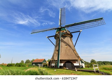 Traditional old windmill the 'Moppemolen' in Rijpwetering, the Netherlands, a historic monument and landmark in the dutch landscape on a summer day with a blue sky