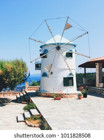 Traditional old windmill on the island of Zakynthos, Greece. Beautiful sunny hot summer day, blue sky, green grass, brick windmill with two windows standing alone on the hill, touristic scenic view.