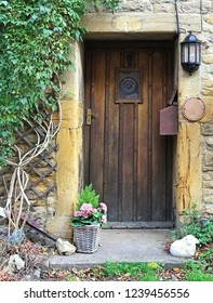 Traditional old wooden door with a wooden surround set in stone. Framed with plants with space for text.