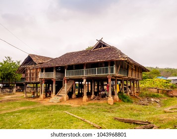 A traditional old wooden house in a blur view of surrounding houses, trees and hill from afar in Shan state of Myanmar under cloudy sky