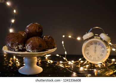 traditional oliebollen, oil dumpling or fritter, with lights, clock and present, for Dutch New Year's Eve