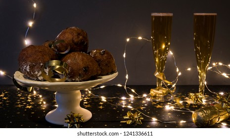 traditional oliebollen, oil dumpling or fritter, with lights, present and champagne, for Dutch New Year's Eve