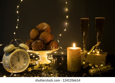 traditional oliebollen, oil dumpling or fritter, with lamps, clock and champagne, for Dutch New Year's Eve.
