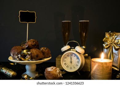 traditional oliebollen, oil dumpling or fritter, with lamps, clock and champagne, for Dutch New Year's Eve