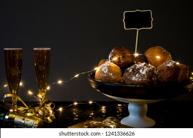 traditional oliebollen, oil dumpling or fritter, with lights and champagne, for Dutch New Year's Eve