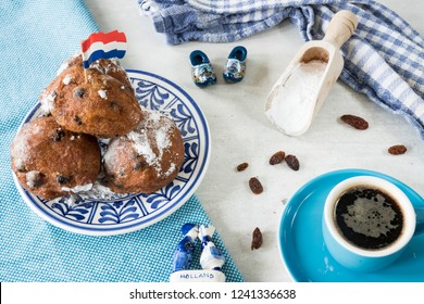 traditional oliebollen, oil dumpling or fritter, on blue plate, for Dutch New Year's Eve. with clogs and flag