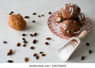 traditional oliebollen, oil dumpling or fritter, on red plate, for Dutch New Year's Eve