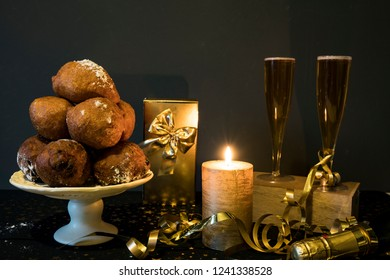 traditional oliebollen, oil dumpling or fritter, with candle, golden gift box and champagne, for Dutch New Year's Eve
