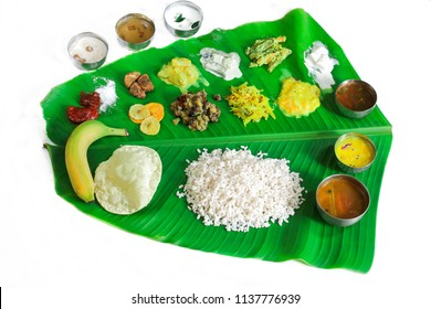 Traditional Onam Feast or Onasadya served in Banana leaf isolated on white with copy space