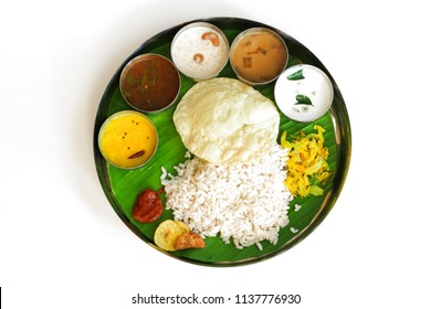 Traditional Onam Feast / South Indian  Vegetarian Thali on banana leaf and round steel plate isolated on white