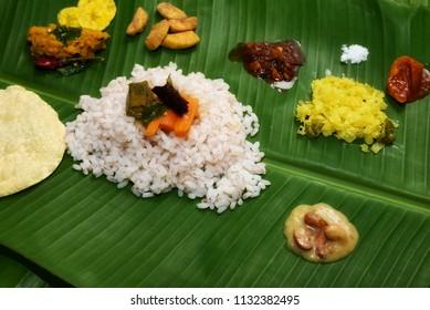 Traditional Onam Sadhya boiled rice served with curries Parippu, Sambar, Rasam, Pulisseri, Kaalan, Avial, Thoran, Olan, Pachadi, Naranga, Papadum, Payasam, Banana, Yogurt, Buttermilk, chips in Kerala.