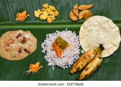 Traditional Onam sadhya, boiled rice, served with curries Parippu, Sambar, Rasam, Pulisseri, Kaalan, Avial, Thoran, Olan, Pachadi, Naranga curry, Papadum, Payasam, Banana, Yogurt or Buttermilk, chips.