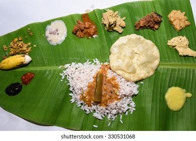 Traditional Onam sadhya, boiled rice, served with curries Parippu, Sambar, Rasam, Pulisseri, Kaalan, Avial, Thoran, Olan, Pachadi, Naranga curry, Papadum, Payasam, Banana, Yogurt or Buttermilk, chips