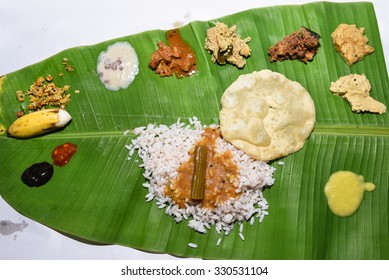 Traditional Onam sadhya, boiled rice, served with curries Parippu, Sambar, Rasam, Pulisseri, Kaalan, Avial, Thoran, Olan, Pachadi, Naranga curry, Papadum, Payasam, Banana, Yogurt or Buttermilk, chips