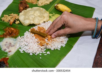 Traditional Onam sadhya Eating with hand, boiled rice with curries Parippu, Sambar, Rasam, Pulisseri, Kaalan, Avial, Thoran, Olan, Pachadi, Naranga curry, Papadum, Payasam, Banana, Yogurt/ Buttermilk
