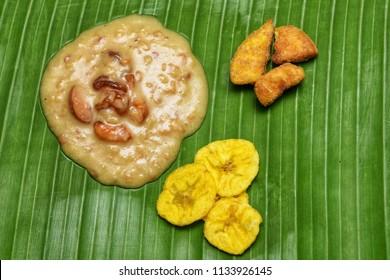 Traditional Onam Sadhya Payasam, Banana chips, Sharkara Upperi on banana leaf Kerala, India.