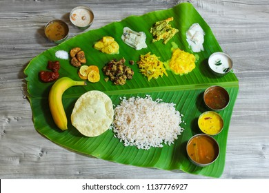 Traditional Onam Sadya / Feast served in fresh banana leaf / Vegetarian meal with rice and curries