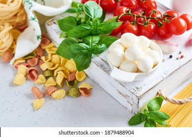 Traditional organic ingredients of italian cuisine : pasta, tomato, garlic, olive oil, mozzarella cheese balls and basil on a light grey slate, stone or concrete background. Space for text.