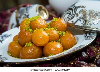 Traditional oriental dessert speciality called luqaimat, fried dough balls in a plate being drizzled with dibs (date syrup). Luqaimat is a popular Arabian dessert that is often eaten during Ramadan.