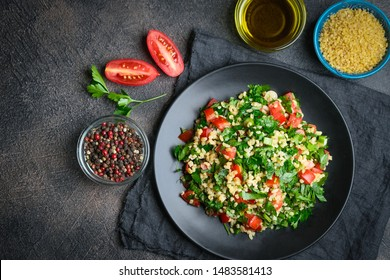 Traditional oriental salad Tabouleh with bulgur and parsley on a dark background top view copy space.