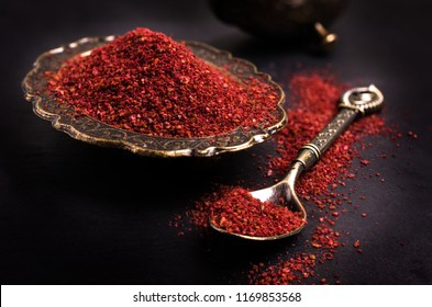 Traditional oriental spice sumac in metallic utensil on dark background. Selective focus.