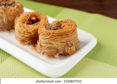 Traditional Oriental sweet bird's nest with honey and nuts close-up. Sweet roll of thin dough. Selective focus. On a wooden background and a green napkin.