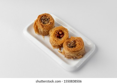 Traditional Oriental sweet bird's nest with honey and nuts close-up. Sweet roll of thin dough. Selective focus. On white background.