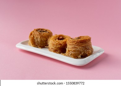Traditional Oriental sweet bird's nest with honey and nuts close-up. Sweet roll of thin dough. Selective focus. On a pink background.