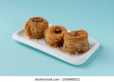 Traditional Oriental sweet bird's nest with honey and nuts close-up. Sweet roll of thin dough. Selective focus. On a blue background.