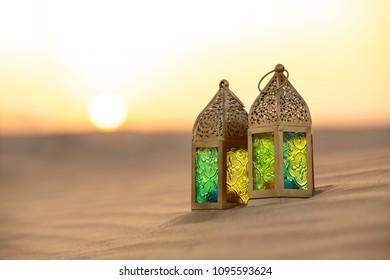 Traditional ornamental arabic lantern with a burning candle in desert during sunset. Festivel greeting card for Ramadan Kareem and Ramadan Mubarak. Dubai, UAE.