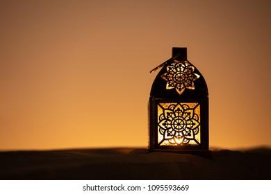 Traditional ornamental arabic lantern with a burning candle in desert after sunset during blue hour. Festivel greeting card for Ramadan Kareem and Ramadan Mubarak. Dubai, UAE.
