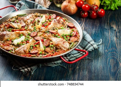 Traditional paella with chicken legs, sausage chorizo and vegetables served in paellera. Spanish cuisine