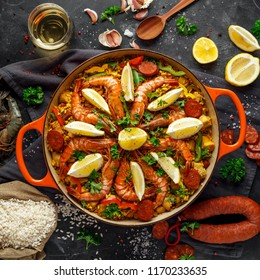 Traditional paella in the fry pan with chicken, tiger prawns, spicy chorizo, lemon and glass of white wine.