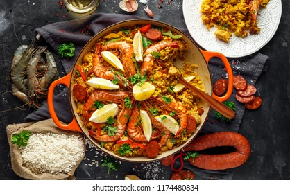 Traditional paella in the fry pan with chicken, prawns, spicy chorizo, lemon and glass of white wine