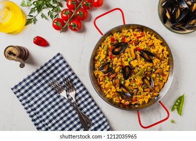 Traditional paella with mussels. Top view. Stone white background.