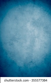 Traditional painted canvas or muslin fabric cloth studio backdrop or background, suitable for use with portraits, products and concepts. Shade of blue, lighter in the center, darker on edges.