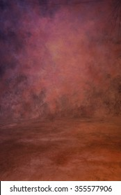 Traditional painted canvas or muslin fabric cloth studio backdrop or background, suitable for use with portraits, products and concepts. Dramatic red, pink and orange blends of color with dark edges.