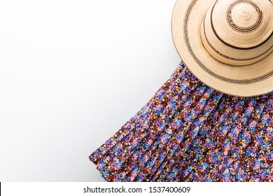 """Traditional painted Panama hat on a white table and a skirt in """"Pollera"""""""