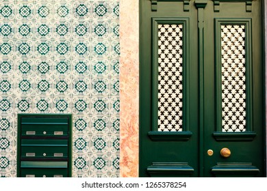 Traditional painted tiles and matching green color postal boxes and entrance door to the building in Lisbon, Portugal.
