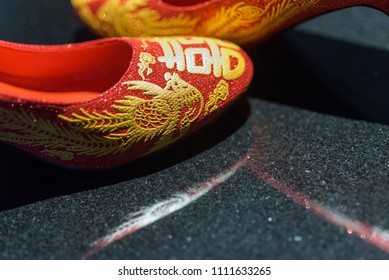 """Traditional pair of red wedding shoes worn by Chinese bride as part of a """"Qipao"""" outfit on wedding day. Te sign on shoes means happiness in wedding day and copy space."""