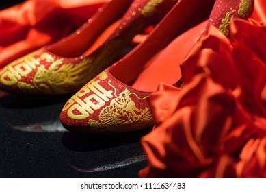 """Traditional pair of red wedding shoes worn by Chinese bride as part of a """"Qipao"""" outfit on wedding day. Deliberate focus on the front of the shoe with shallow depth of field and copy space."""